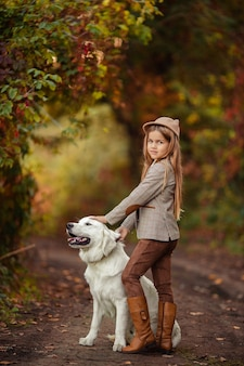 Belle fille et un animal retriever pour une promenade dans le parc d'automne