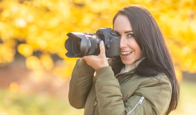 Belle fille avec un appareil photo professionnel prenant des photos à l'extérieur dans une nature d'automne.