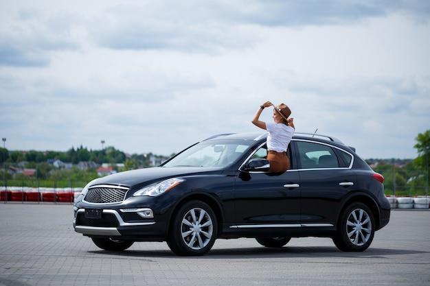 Une belle fille d'apparence européenne avec des lunettes et un chapeau marron se tient près d'une voiture noire. jeune femme avec voiture en stationnement