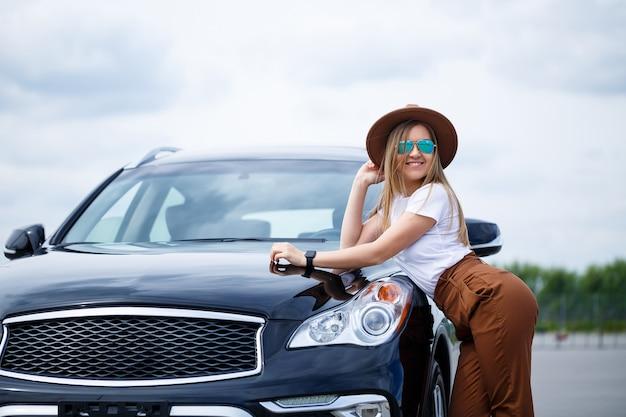 Une belle fille d'apparence européenne portant des lunettes et un chapeau marron se tient près d'une voiture noire. séance photo près de la voiture.