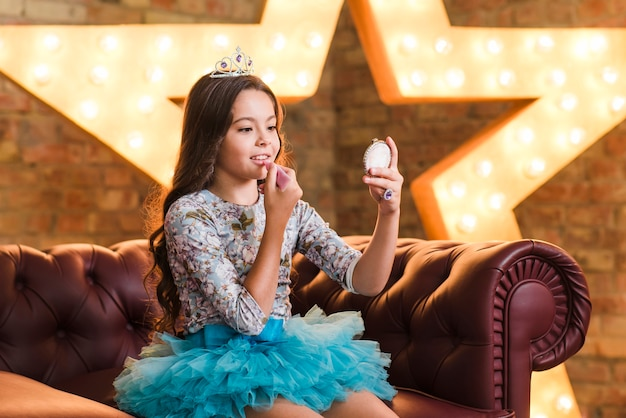 Belle fille appliquant le rouge à lèvres assis sur le canapé contre l'étoile rougeoyante