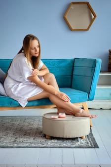 Belle fille, appliquer une crème pour les pieds à la maison, assise sur le canapé en robe de soie blanche