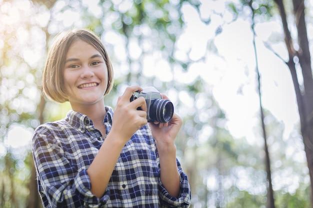 Belle fille apprendre à utiliser un appareil photo proche de la nature.
