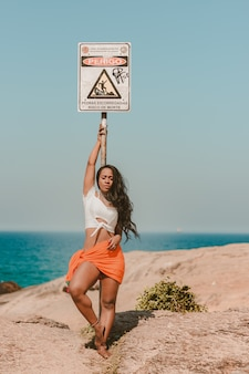 Belle fille appuyée contre un panneau de danger sur la plage