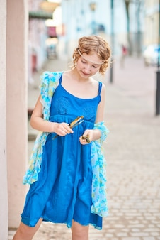 Belle fille d'artiste dans la rue en robe bleue avec gland à la main