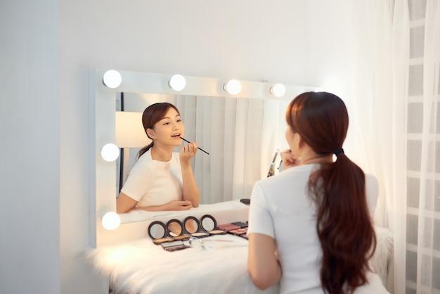 Belle fille asiatique appliquant le rouge à lèvres devant le miroir. concept de maquillage