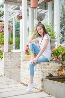 Belle fille asiatique assise devant sa maison et sourit