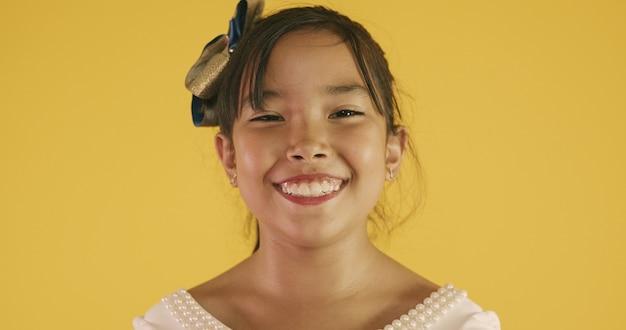Belle fille asiatique assise sur fond jaune. heureuse petite fille asiatique souriante.
