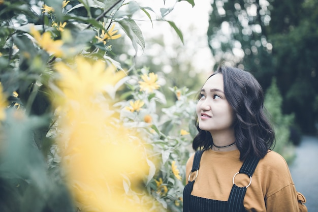 Belle fille asiatique dans un jardin, souriant