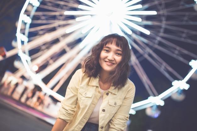Belle fille asiatique dans un parc d'attractions la nuit, souriant