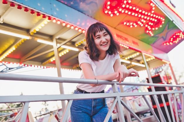 Belle fille asiatique dans un parc d'attractions, souriant