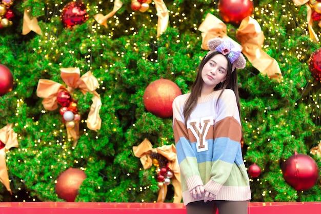 Belle fille asiatique dans un pull coloré sourit joyeusement devant l'arbre de noël. dans le thème de la célébration de la nouvelle année.