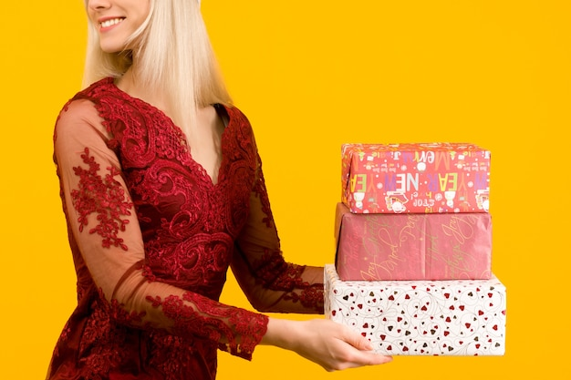 Une belle fille asiatique dans une robe rouge tenir en mains cadeaux sur fond jaune
