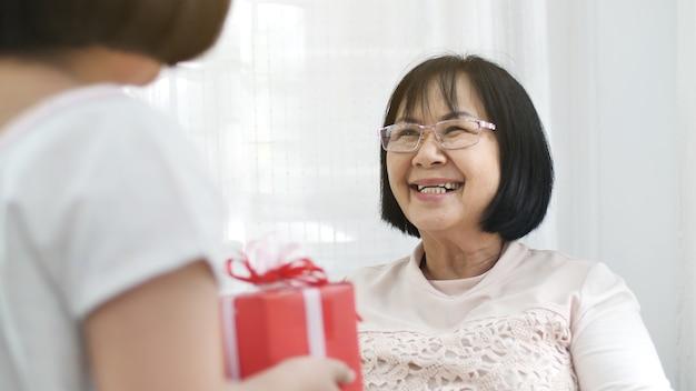 Belle fille asiatique donne une boîte cadeau spatiale à sa grand-mère