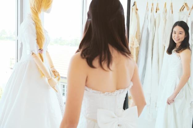 Belle fille asiatique essayer une robe de mariée dans la boutique.
