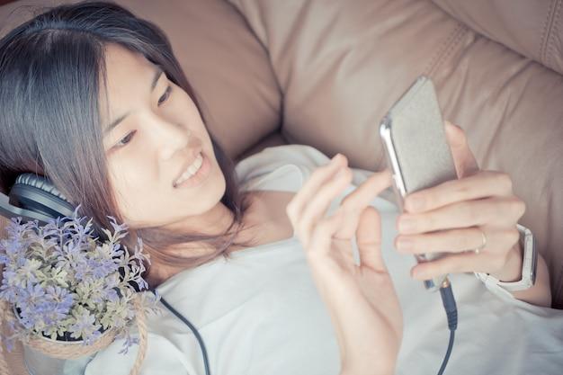 Belle fille asiatique est écouter de la musique sur smartphone