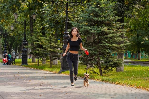 Belle fille asiatique jogging dans le parc en été avec son chien yorkshire terrier