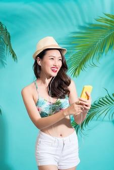 Belle fille asiatique avec maquillage professionnel et coiffure élégante chantant et dansant