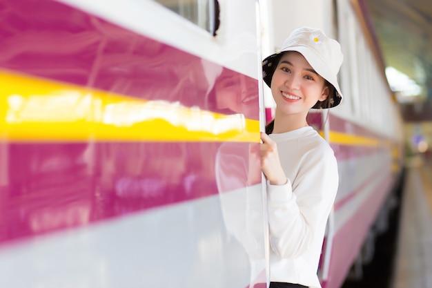 Une belle fille asiatique marchait dans le train pour voyager pendant que le train était garé sur le quai
