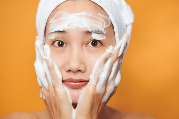 Belle fille asiatique mettant de la crème sur son visage. isolé sur fond orange.