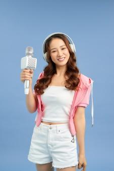 Belle fille asiatique avec microphone chante et casque isolé sur fond bleu.