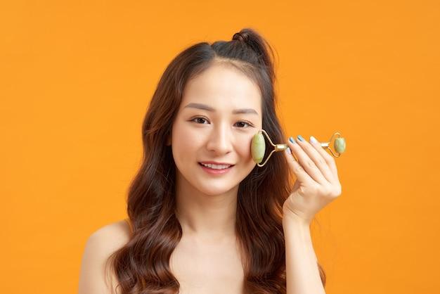 Belle fille asiatique nue massant le visage avec un rouleau de jade isolé sur orange jaune