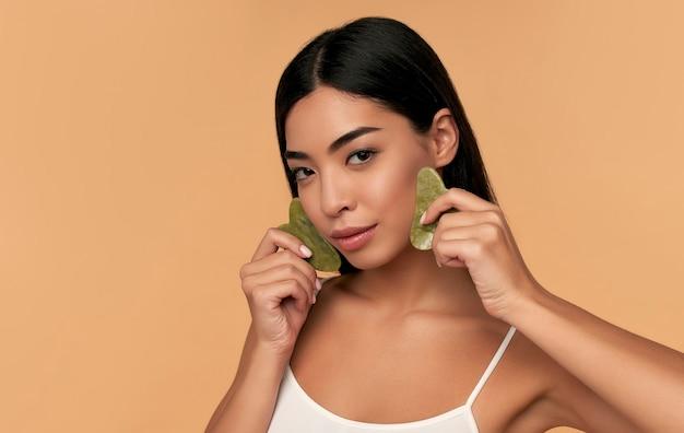 Belle fille asiatique avec la pierre de quartz de beauté de gua sha pour le massage sur le beige
