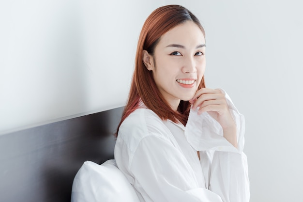 Belle fille asiatique porte chemise blanche sourire dans sa chambre le matin