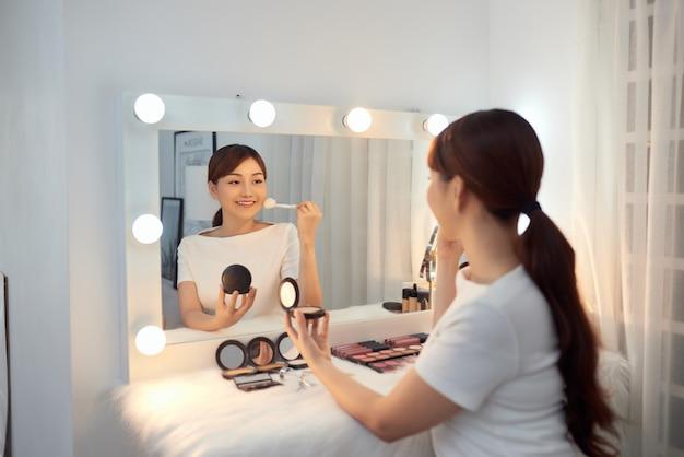 Belle fille asiatique regardant dans le miroir et appliquant le cosmétique avec une grande brosse