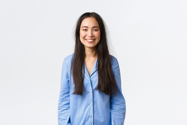 Belle fille asiatique souriante en pyjama bleu qui a l'air ravie, a les cheveux en désordre après s'être réveillée et s'est levée du lit, debout sur fond blanc, a passé une bonne nuit de sommeil, exprime sa satisfaction