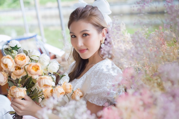 Belle fille asiatique tenant des fleurs avec fond naturel.