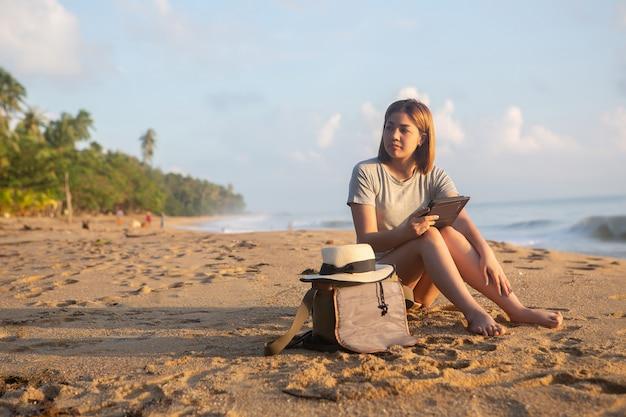 Belle fille assise asseyez-vous et jouez smartphone sur la plage