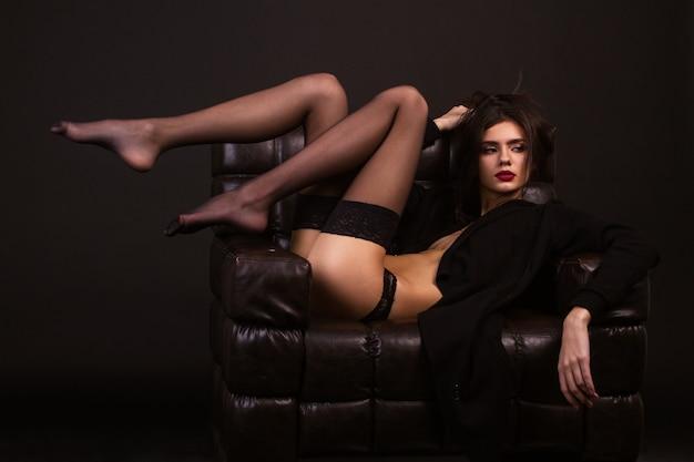 Belle fille assise sur une chaise en cuir avec ses jambes vers le haut. bas noirs.