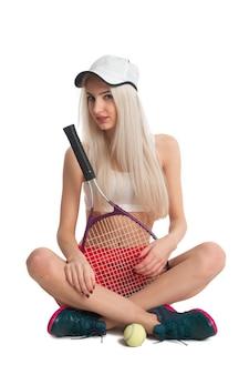Belle fille assise dans une jupe rouge avec une raquette de tennis et une balle sur fond blanc