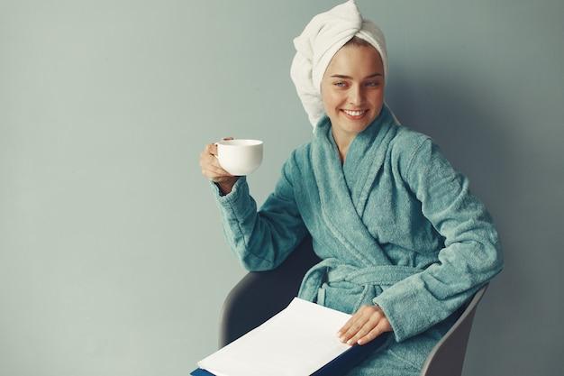 Belle fille assise dans un peignoir bleu