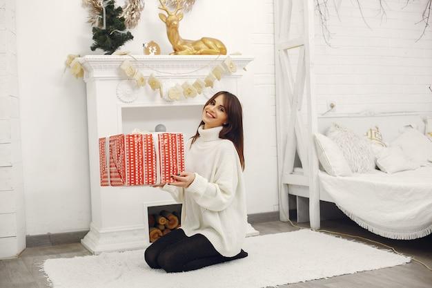 Belle fille assise dans une pièce avec des cadeaux de noël