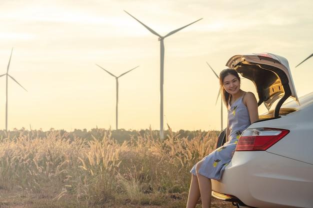 Belle fille assise derrière la voiture et elle sourit au fond du crépuscule est une éolienne.