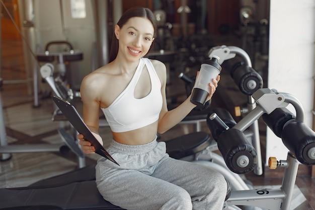 Une belle fille assise avec de l'eau dans une salle de sport