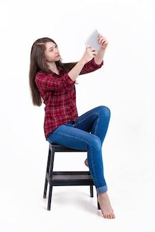 Belle fille assise sur un escabeau dans le studio et se penche sur la tablette