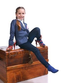Belle fille assise sur une grande boîte et essayant des chaussures de mamans