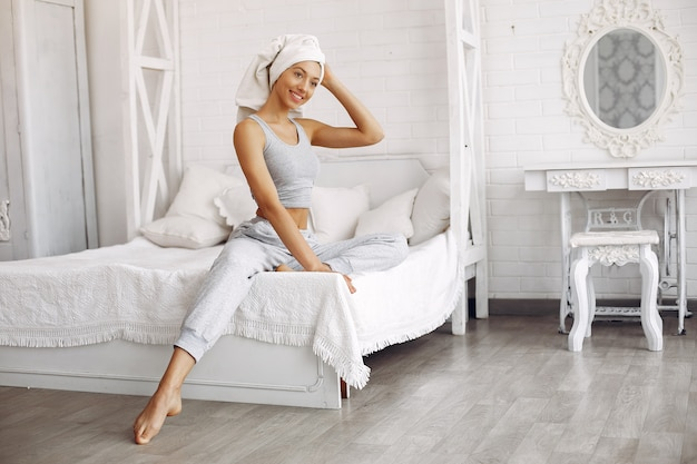 Belle fille assise sur un lit avec des produits de beauté