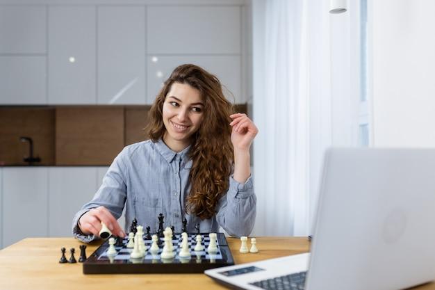Belle fille assise à la maison et jouer aux échecs en ligne avec un ordinateur portable
