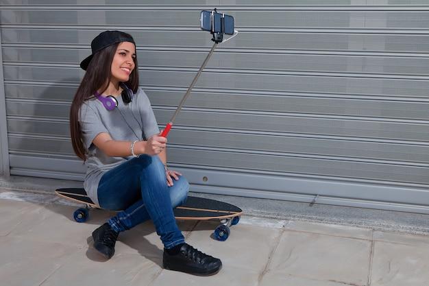 Belle fille assise sur une planche à roulettes prenant selfie