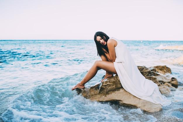 Belle fille assise sur un rocher sur la mer de la plage