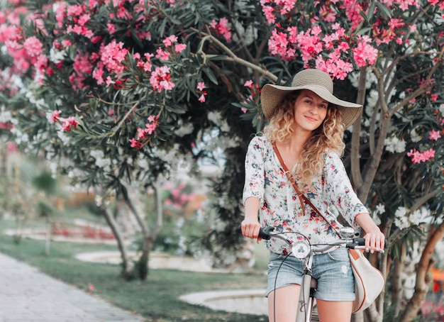 Belle fille assise sur un vélo et souriant en chemise texturée blanche pendant la journée.