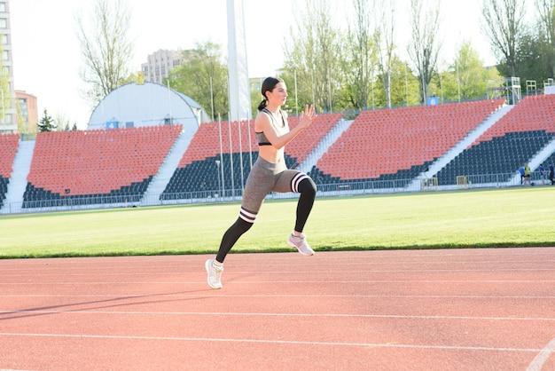 Belle fille athlétique qui court autour du stade