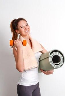 Belle fille athlétique tenant un tapis et des haltères, debout contre le mur avec une serviette autour du cou