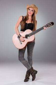 La belle fille au chapeau de cowboy et à la guitare acoustique.