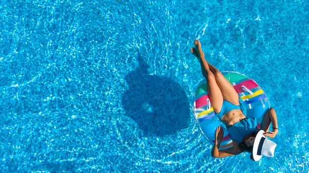 Belle fille au chapeau dans la piscine vue aérienne de dessus, jeune femme se détend et nage sur l'anneau gonflable et s'amuse dans l'eau en vacances en famille, tropical resort de vacances