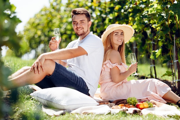 Belle fille au chapeau et jeune homme se détendre dans le vignoble